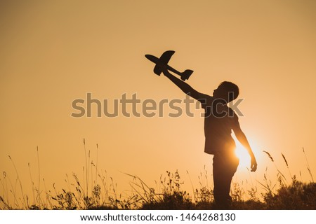 Black silhouette of young caucasian kid isolated on sunny golden sunset sky background. Boy playing toy plane outside on grassy summer hill. Setting big goals and dreaming about happy future concept.