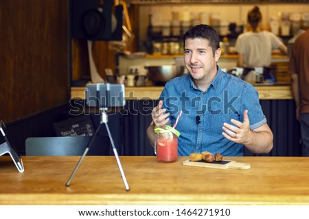 Social media influencer or food blogger creating content inside small restaurant – man sharing online food review using smartphone on tripod and lavalier, smiling content creator vlogger filming video