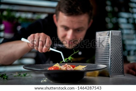 cook puts greens on a dish #1464287543