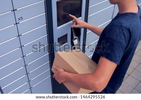 Man client using automated self service post terminal machine or locker to deposit a parcel for storage #1464295526