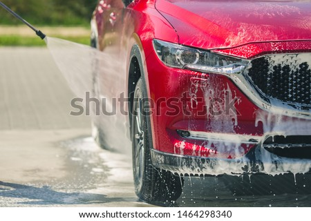 Manual car wash with pressurized water in car wash outside. Summer Car Washing. Cleaning Car Using High Pressure Water. Washing  with soap. Close up concept. #1464298340