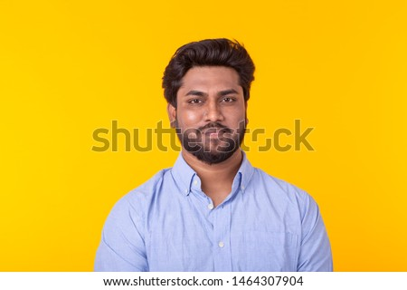 Indian handsome man wearing blue shirt on yellow background #1464307904