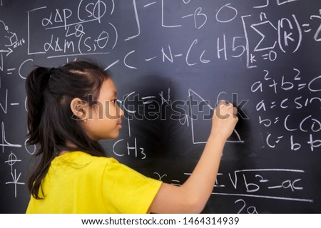 Female elementary school student writes mathematics formula on the blackboard while studying in the classroom