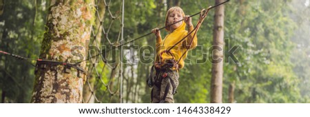 Little boy in a rope park. Active physical recreation of the child in the fresh air in the park. Training for children BANNER, LONG FORMAT #1464338429
