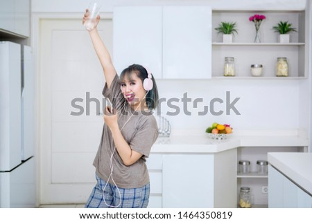 Beautiful woman holds a glass of water while enjoying music by using a headset in the kitchen #1464350819