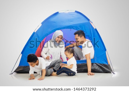 Picture of Muslim family looks happy while enjoying a camping holiday in the studio, isolated on white background