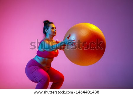 Young caucasian plus size female model's doing exercises on gradient purple background in neon light. Training lower body with  ball. Concept of sport, healthy lifestyle, body positive, equality. #1464401438