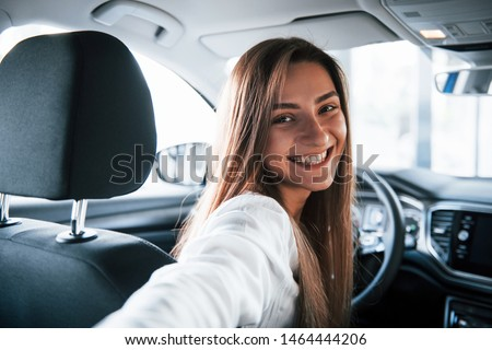 Making selfie. Cheerful female driver is in her new car. Interior of modern automobile. #1464444206