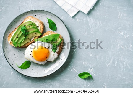 Avocado Sandwich with Fried Egg - sliced avocado and  egg on toasted bread with arugula for healthy breakfast or snack. #1464452450