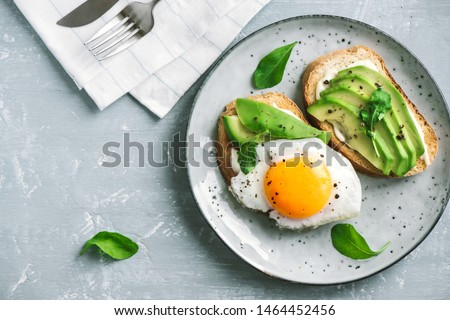 Avocado Sandwich with Fried Egg - sliced avocado and  egg on toasted bread with arugula for healthy breakfast or snack. #1464452456
