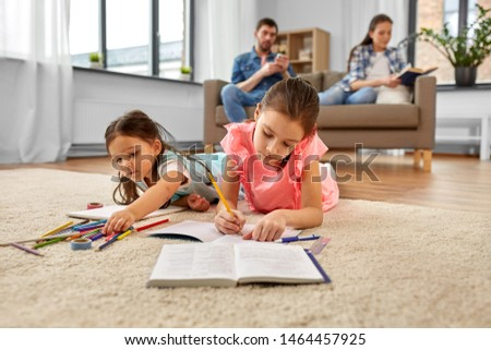 family, leisure and childhood concept - happy sisters lying on floor and drawing and doing homework at home #1464457925