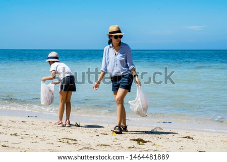 Two female volunteers clean up the beach by picking plastic waste in the water #1464481889
