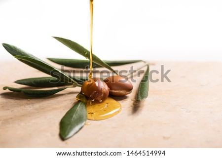 Argan oil, used for cosmetics, pouring over two argan seeds on a stone table. #1464514994