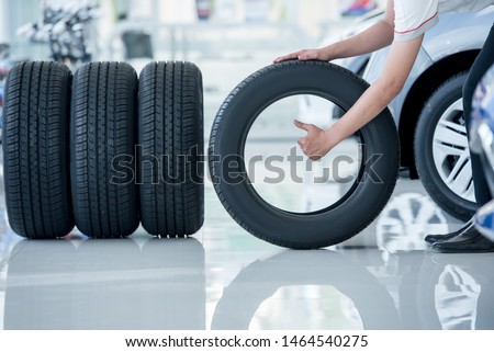 4 new tires that change tires in the auto repair service center, blurred background, the background is a new car in the stock blur for the industry, a four-wheeled tire set at a large warehouse #1464540275