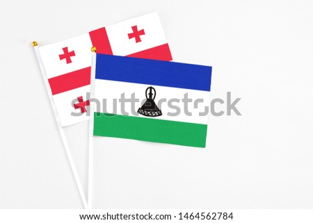 Lesotho and Georgia stick flags on white background. High quality fabric, miniature national flag. Peaceful global concept.White floor for copy space. #1464562784