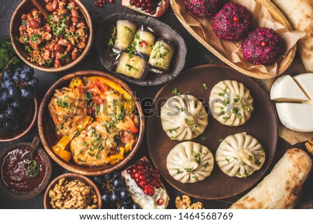Traditional Georgian cuisine background. Khinkali, phali, chahokhbili, lobio, cheese, eggplant rolls on dark background, top view. #1464568769