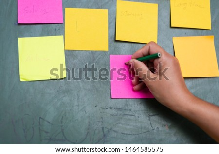 Close up woman hand writing colorful note sticky for brainstorm and share idea strategy workshop business.Brainstorming concept. #1464585575