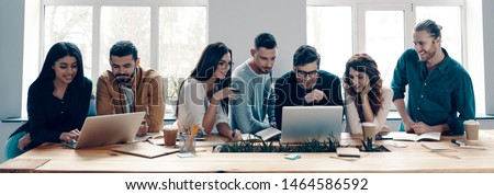 Successful team. Group of young modern people in smart casual wear using modern technologies while working in the creative office #1464586592
