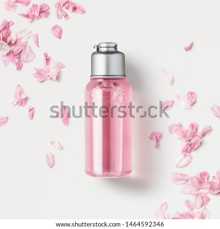cosmetics packaging design concept or mock-up with blank transparent bottle with pink liquid soap or shower gel on a white surface surrounded by delicate cherry flower petals, top view / flat lay #1464592346