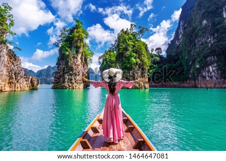 Beautiful girl standing on the boat and looking to mountains in Ratchaprapha Dam at Khao Sok National Park, Surat Thani Province, Thailand. #1464647081