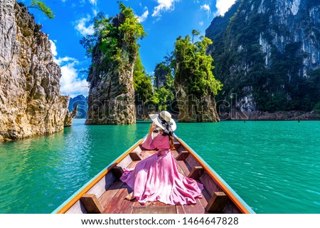 Beautiful girl sitting on the boat and looking to mountains in Ratchaprapha Dam at Khao Sok National Park, Surat Thani Province, Thailand. #1464647828