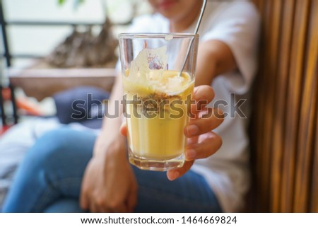 Woman holding a Vietnamese egg coffee hot and cool in the white coffee mug, cup in HANOI VIETNAM #1464669824
