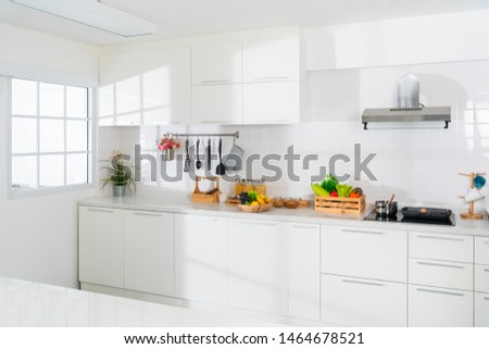 Modern white kitchen with counter and white details, minimalist interior, Full set of kitchen equipment, pan, pot, electric hob, flipper, vegetable, fruit. #1464678521