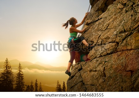Beautiful Woman Climbing on the High Rock at Foggy Sunset in the Mountains. Adventure and Extreme Sport Concept #1464683555