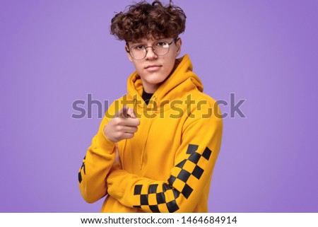 Serious youngster with curly hair wearing nerdy glasses and yellow hoodie and pointing at camera while standing against violet background