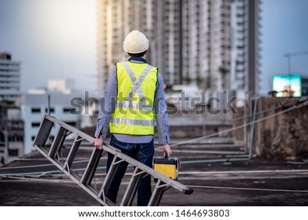 Asian maintenance worker man with safety helmet and green vest carrying aluminium step ladder and tool box at construction site. Civil engineering, Architecture builder and building service concepts #1464693803