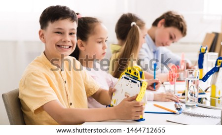 Stem education and early development. Happy child creating robot at lab, boy smiling to camera #1464712655