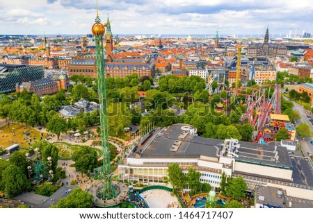 COPENHAGEN, DENMARK - JUNE 2019 - Aerial view of the Tivoli Gardens amusement park with people, visitors, attractions and rides. Urban view of the city of Copenhagen in Denmark, Europe #1464717407