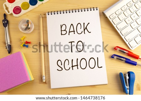 School supplies on wooden background. Back to school concept with text in the notepad. #1464738176