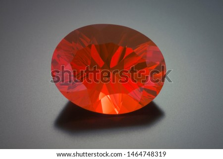 A large oval faceted mexican fire opal sits on a reflective gray background. The stone is mostly red in color.