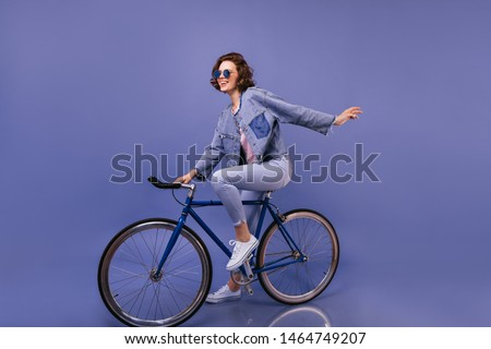 Amazing woman in spring clothes sitting on bicycle. Indoor portrait of lovely girl in sunglasses fooling around on violet background. #1464749207