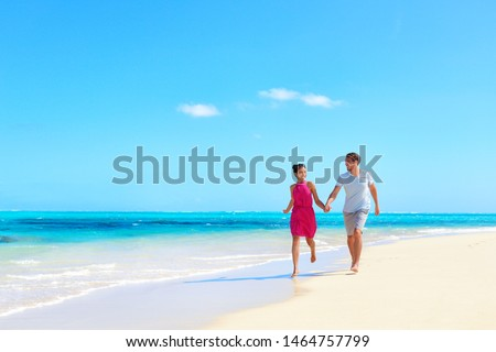 Beach vacation honeymoon paradise travel destination - Young couple in love walking holding hands in idyllic holiday background. #1464757799