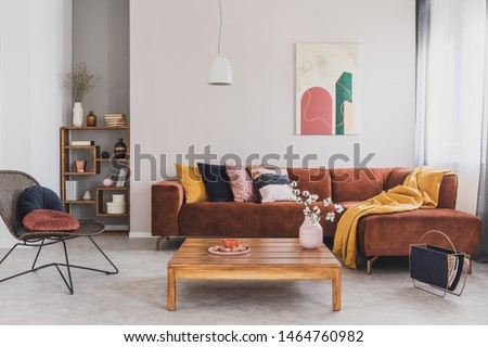 Flowers in vase on wooden coffee table in fashionable living room interior with brown corner sofa with pillows and abstract painting on the wall #1464760982
