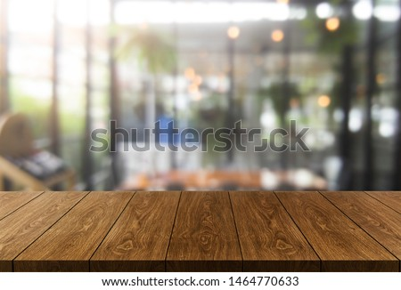Wood table in blurry background of modern restaurant room or coffee shop with empty copy space on the table for product display mockup. Interior restaurant counter design concept. #1464770633