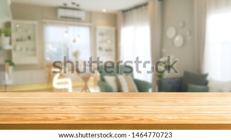 Wood table in modern home room interior with empty copy space on the table for product display mockup. Furniture design and home decoration concept. #1464770723