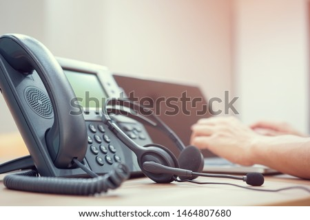 close up on telephone office desk with employee call center man hand typing on a keyboard at desktop pc for working in operation room , communication technology concept Royalty-Free Stock Photo #1464807680