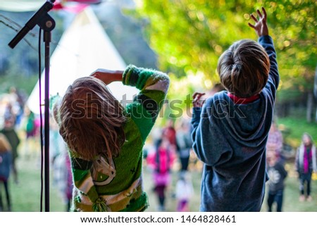Fusion of cultural & modern music event. Children are seen from behind, standing on stage next to a mic stand during a family friendly music festival combing different cultures. #1464828461