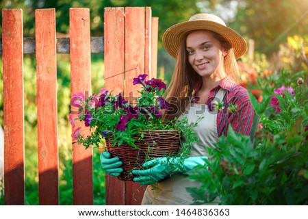 Portrait of happy florist gardener with flower pot of petunia outdoors. Gardening and floriculture. Growing flower in home garden  #1464836363