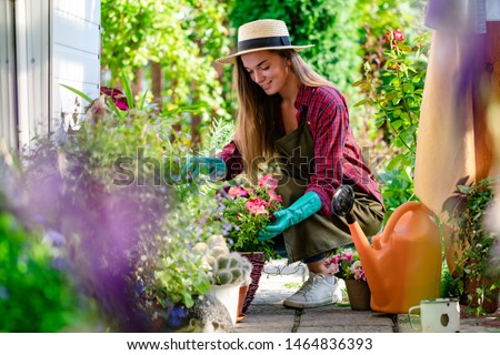 Happy gardener woman in gloves and apron plants flowers on the flower bed in home garden. Gardening and floriculture. Flower care #1464836393