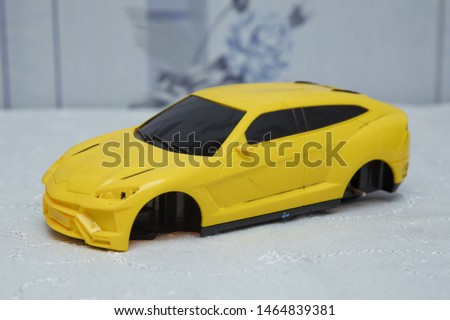 Not wheelchairs yellow baby car . Closeup of a yellow baby car on a white background . Broken yellow toy car