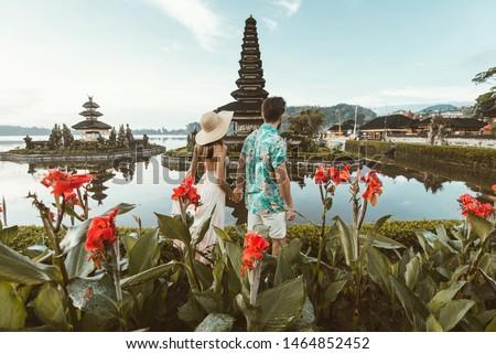 Couple at the Pura Ulun Danu Bratan, Bali. Hindu temple surrounded by flowers on Bratan lake, Bali. #1464852452