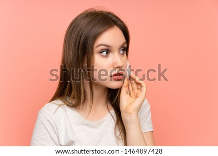 Teenager girl removing makeup from her face with cotton pad #1464897428