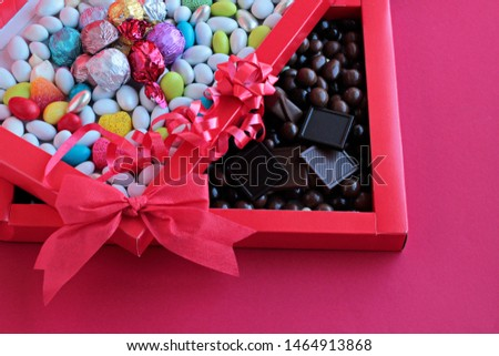 Luxury,Colorful Almond Candies and Madlen Chocolate in red color carton box with red bow and ribbon.Unedit,original,as taken  conceptual image for celebrations.