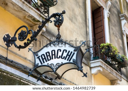 An old-fashioned Tabacchi, or Tobacco, sign above a shop in Venice, Italy. Royalty-Free Stock Photo #1464982739