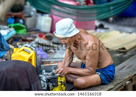 Mangrove Forest Learning Center Phra Chedi Klang Nam - Rayong: 21 June 2019, male fishermen are repairing engines for fishing to live, coastal road Pak Nam Subdistrict, Thailand #1465166318