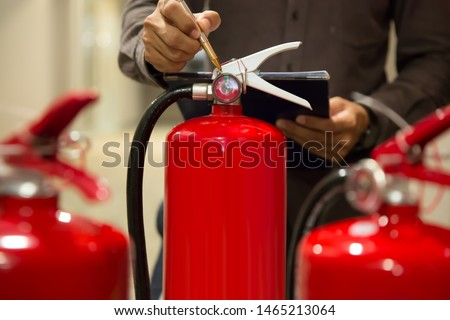 Engineers are checking Pressure gauge on fire extinguishers to prepare for use. #1465213064